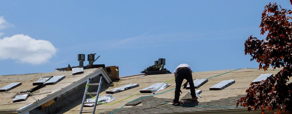 Roofing Companies in Franklin Tn - Roof repair, worker with replacing gray tiles shingles on house being applied