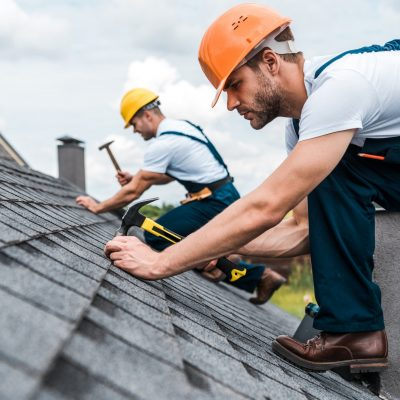 Murfreesboro Roofing - selective focus of handsome handyman repairing roof with coworker